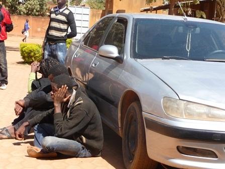 Les cyberdélinquants présumés (assis) adossés à leur véhicule 406 acquis avec l'argent de leurs forfaits. Photo: Burkina24