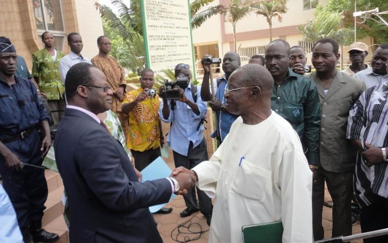Poignée de mains entre  Vincent Zakané et Mamadou Nama après la remise du message des syndicats,  à l'occasion de la fête du travail le 1er mai 2013 (Ph : B24)