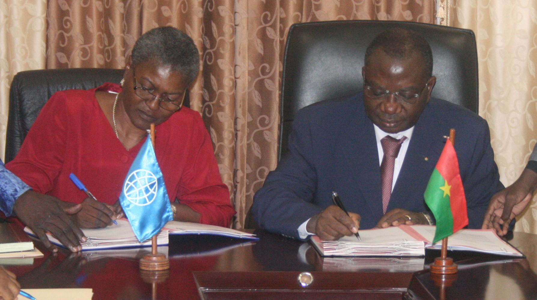 Le ministre des Finances (d.) et la représentante résidente de la BM paraphant le doculent (Ph : B24)
