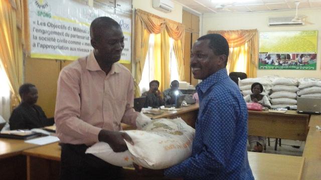 Le représentant du SP/CNLS-IST, Joachim Ouédraogo, remettant symbolique des kits alimentaires  à une ONG (Ph : B24)