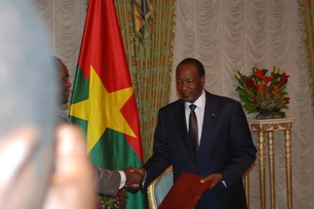 Le Président du Faso recevant le rapport des mains du Ministre d'État, Arsène Yé. ©Burkina 24