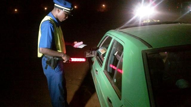 Un agent de la brigade de ville de Bogodogo contrôlant un taxi derrière la gare Ouagarinter (Ph : B24)