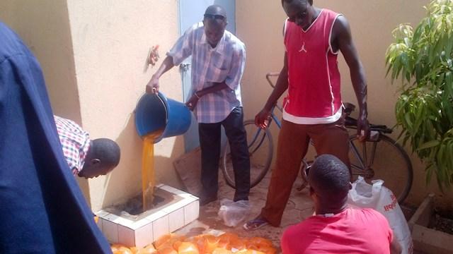 Youssouf Traoré, le gérant d'Ô Fadila, procédant lui-même au vidage des sachets d'eau (Ph : B24)