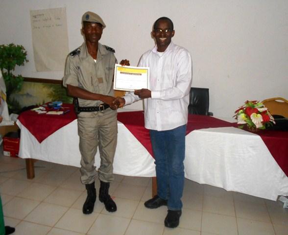 Le directeur d'Amnesty Burkina remettant un certificat de formateur à un  policier à l'issu de la formation. ©Amnesty Burkina