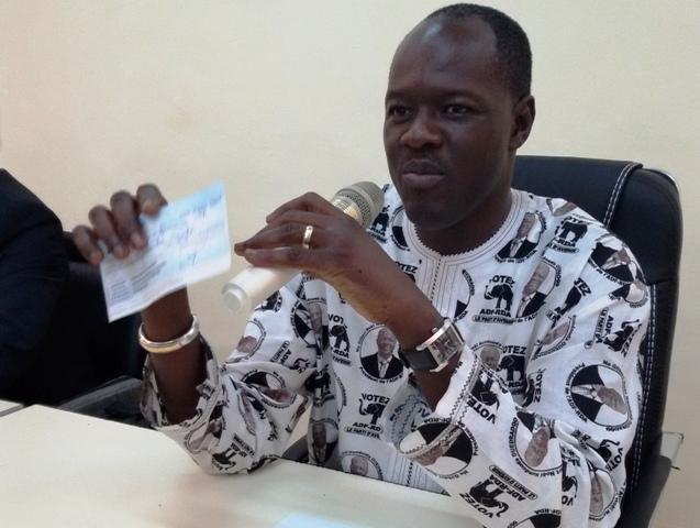 Le président du parti, Gilbert N. Ouédraogo, tenant le chèque qui sera remis au ministère de la santé ( © DR)