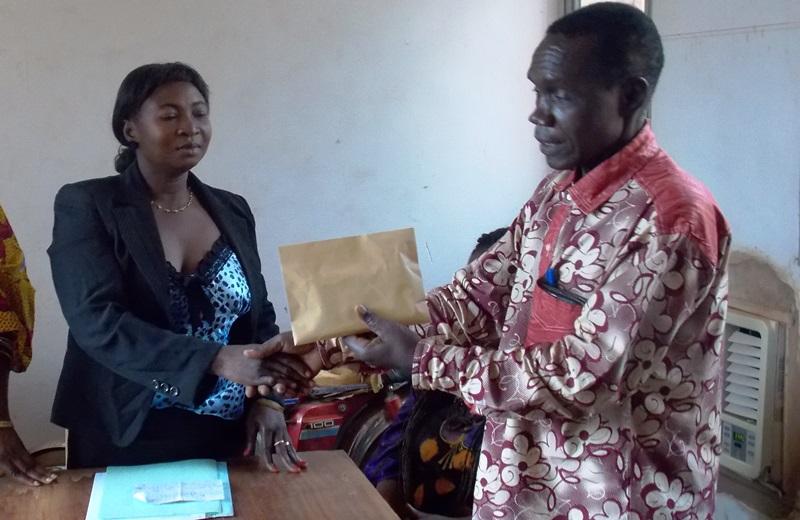 Adèle Ouédraogo, SG de l'association Soubo, remettant l'enveloppe au directeur provinciale de l'action sociale, Lambert Ouédraogo.jpg