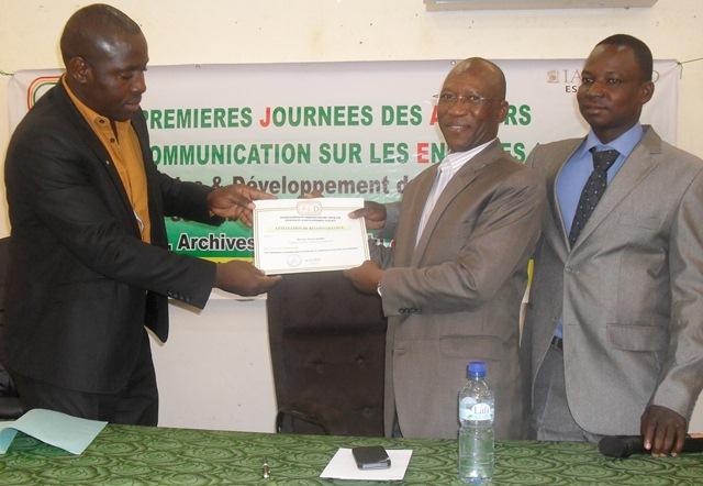 Une attestation de reconnaissance remise au Dr Firmin Gouba (milieu) avec à droite, Grégoire Bazié, président de la JED