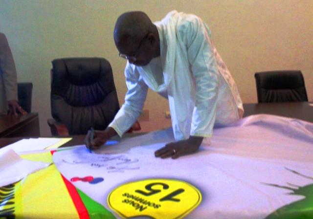 Le Président du CNT en train d'apposer sa signature sur la banderole / Copyright Burkina24