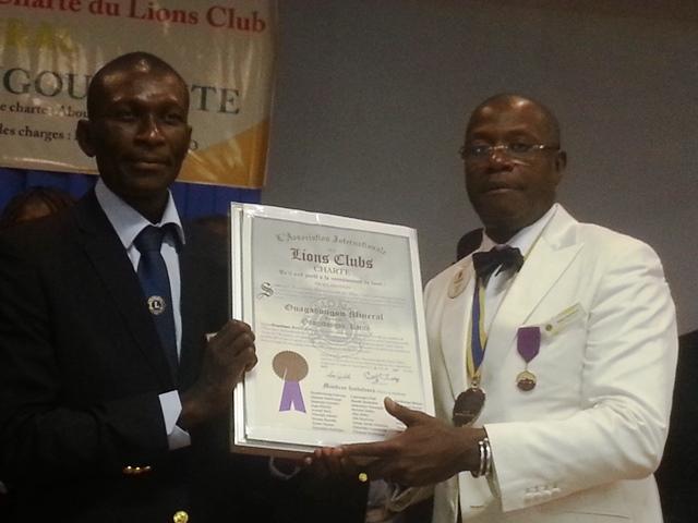 Fabrice Yago en noir recevant la charte des mains du gouverneur