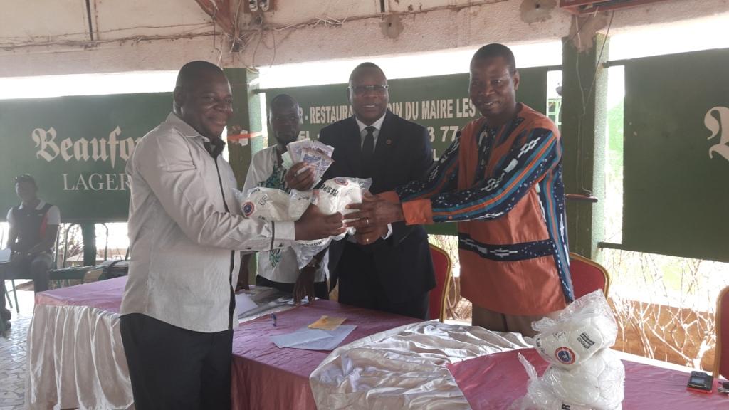 Le représentant de l'ASEC-K recevant son soutien des mains du donateur (costume-cravate) et du haut commissaire du Boulkiémdé
