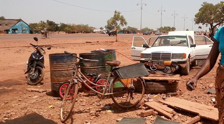 Ce laveur d'engins attend la précieuse manne pour satisfaire ses clients © Burkina24