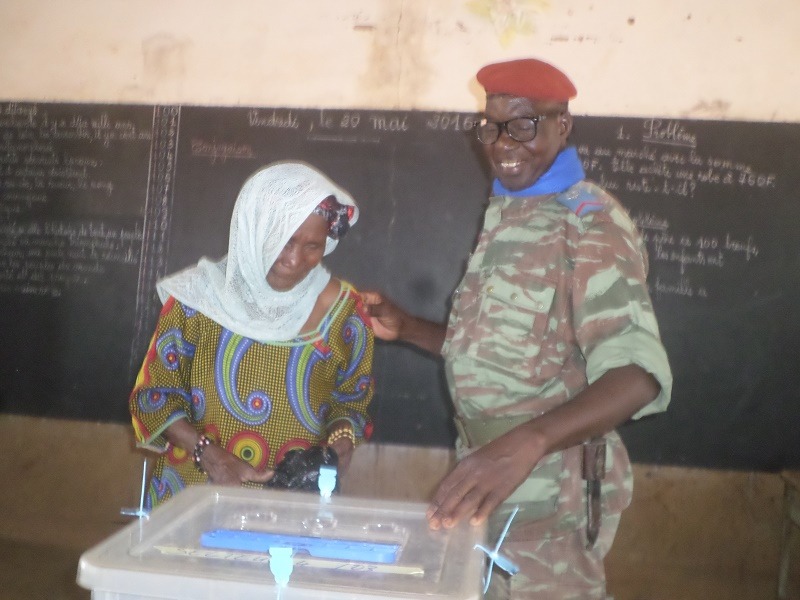L'agent de sécurité aidant une électrice à voter