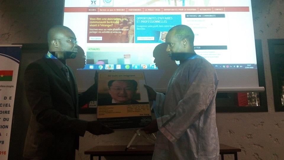 Abel Rahmane Diop remettant au ministre Alpha Barry l'une des images d'une campagne valorisant l'importance des migrants dans le monde