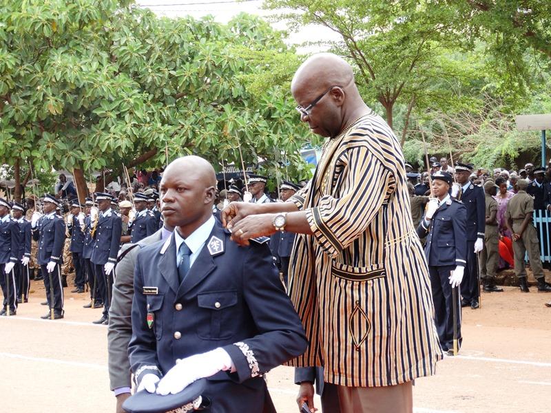 Le ministre de la sécurité intérieure portant au major de la Promotion des élèves commissaires ses épaulettes de commissaire de police. © Burkina24