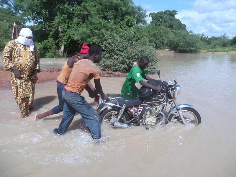 Des jeunes aidant un motocycliste à traverser le pont