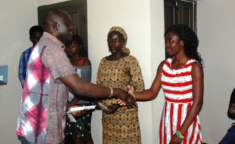Me Gilbert Noël Ouédraogo remettant une enveloppe à la première des nouveaux bacheliers primés.