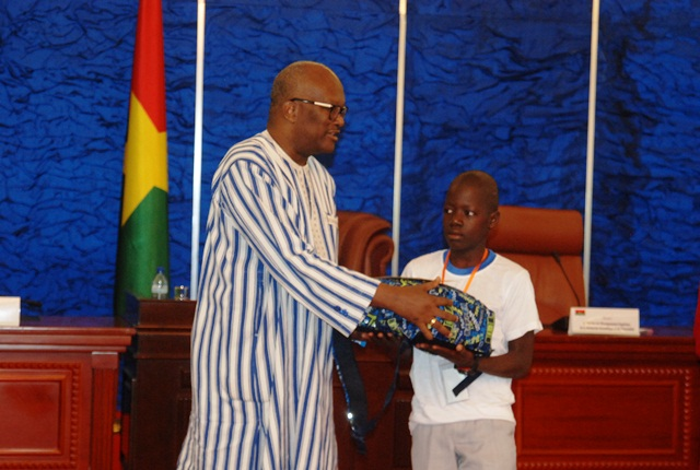 Le premier du CEP session de 2016 recevant son lot de récompense des mains du président du Faso