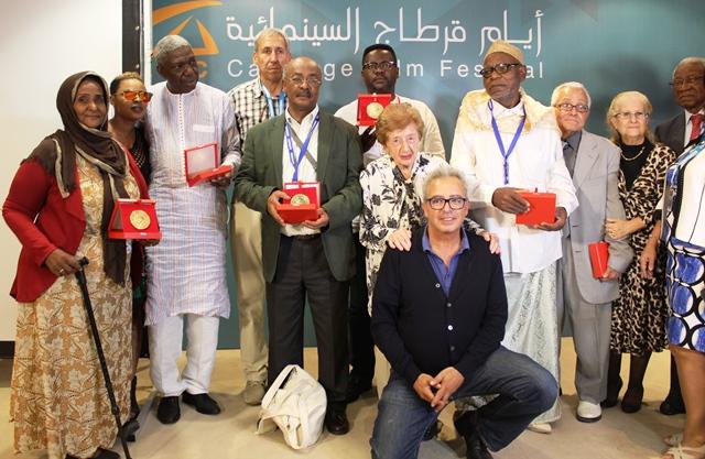 Les pionniers du cinéma (médaille en main ) posant avec le directeur du festival (assis)